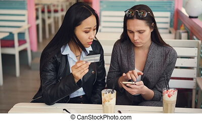 Happy girls Asian and Caucasian are making online payment with bank card paying in internet shop sitting at table in cafe then smiling and doing high-five.