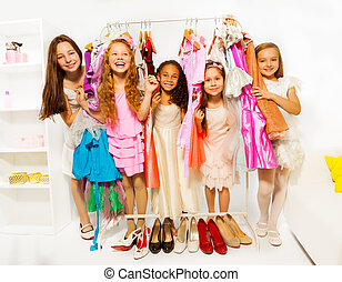 Happy girls during shopping choosing clothes