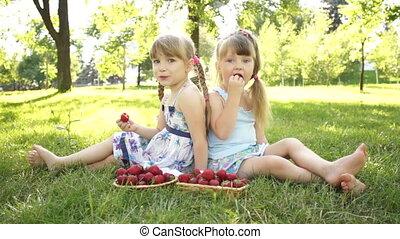 Happy girls eating strawberries.