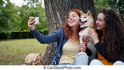 Happy girls friends taking selfie in park with cute dog using smartphone camera