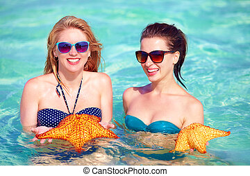 happy girls holding star fish, summer vacation