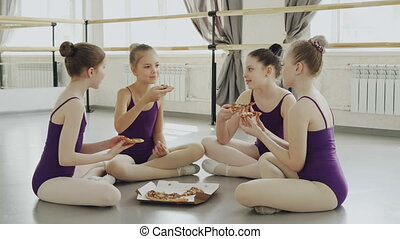 Happy girls in bright leotards are eating pizza and talking while sitting on floor of ballet studio together. Tasty food, communication and children concept.