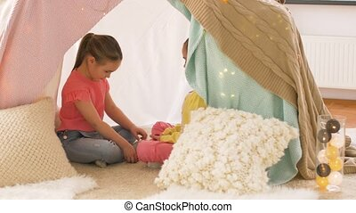 happy girls in kids tent playing tea party at home -...