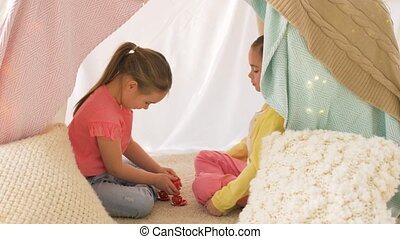 happy girls in kids tent playing tea party at home