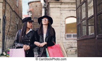 Happy girls in trendy clothing are walking arm-in-arm along...