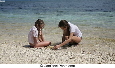 Happy girls playing with sand on beach in summer.