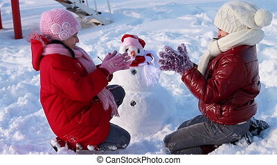 Happy girls playing with snowman