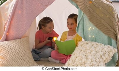 happy girls reading book in kids tent at home