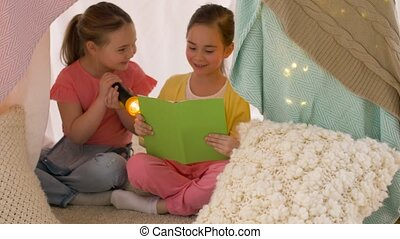 happy girls reading book in kids tent at home - childhood,...
