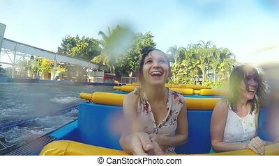 Happy girls riding an water attraction in the amusement park in slow motion. 1920x1080