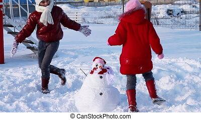Happy girls running around snowman