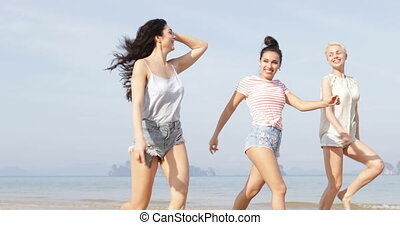 Happy Girls Walking On Beach Jumping, Cheerful Young Women...