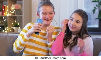 happy girls with smartphone and earphones at home - people, ...