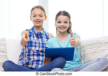 happy girls with tablet pc and showing thumbs up