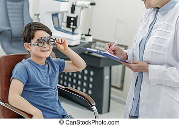Happy glancing child in optic clinic - Cheerful little boy...