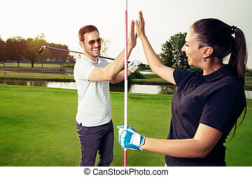 Happy golf player couple giving high five while standing on field