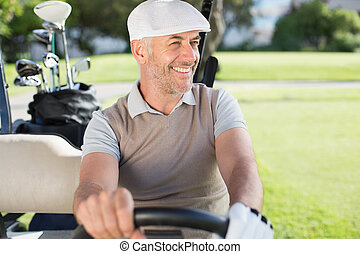 Happy golfer driving his golf buggy on a sunny day at the...