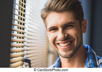 student smiling in front of a window
