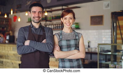 Happy good-looking waiters are standing inside new cafe with...