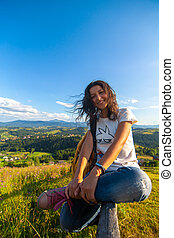 Happy gorgeous girl enjoy hills view sitting in flower field on the hill with breathtaking nature landscape