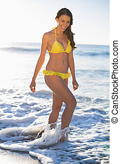 Happy gorgeous woman in yellow bikini