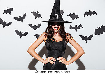 Happy gothic woman in witch halloween costume standing and...