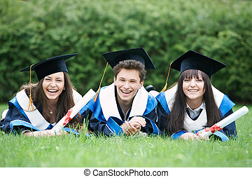 happy graduate students - group of three graduation students...