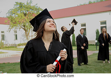 Happy graduate with diploma in hand looking at the sky