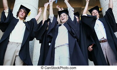 Happy graduated students raising their arms in front of the...