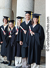 Happy graduates posing in single line - Happy smiling...