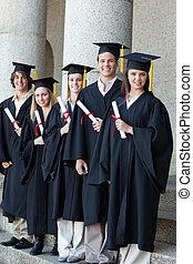 Happy graduates posing in single line - Happy smiling...