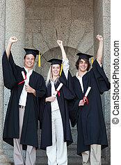 Happy graduates raising arm