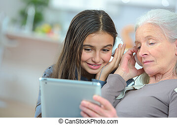 happy grand daughter and grandmother playing with a tablet