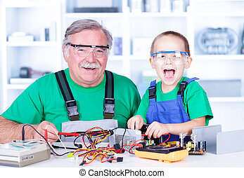 Happy grandfather and grandchild working in workshop - Happy...