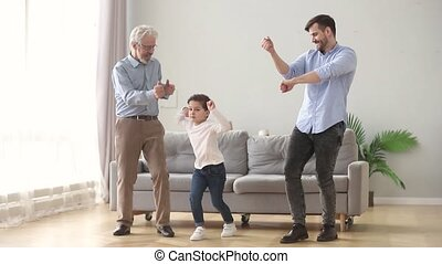 Happy grandfather dad and child son laughing dancing at home