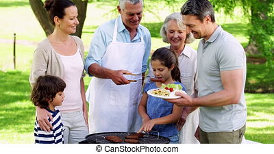 Happy grandfather serving burgers at family barbecue in the...