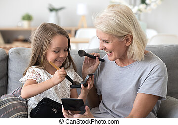 Happy grandma and granddaughter have fun doing make up