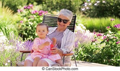 happy grandmother and baby granddaughter at garden - family...