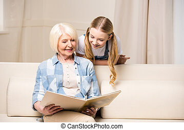 Happy grandmother and granddaughter looking at photo album at home