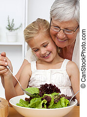 Happy grandmother cooking a salad with granddaughter