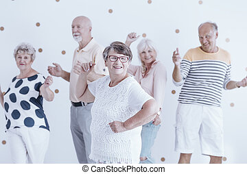 Happy grandmother dancing with friends
