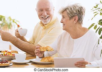 Happy grandmother eating breakfast