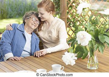 Happy grandmother enjoying time with friendly nurse on the terrace of sanatorium