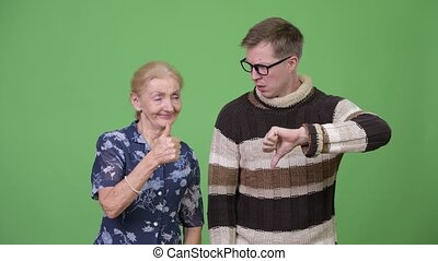 Happy grandmother giving thumbs up while upset grandson giving thumbs down