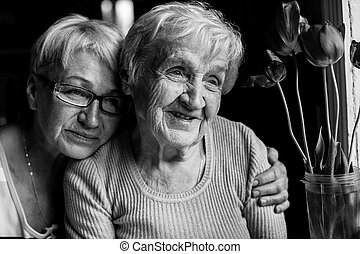 Happy grandmother with her adult daughter. Black and white photography.