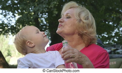 Happy grandmother with her grandchild  having fun in summer park