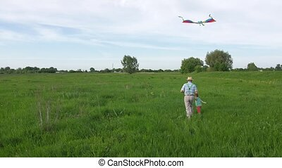 Back view of playful grandfather and grandson running with colorful kite across green meadow enjoying active leisure in countryside. Little boy holding grandpa's hand and flying kite hopping on grass