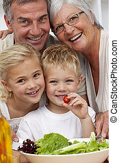 Happy grandparents eating a salad with grandchildren