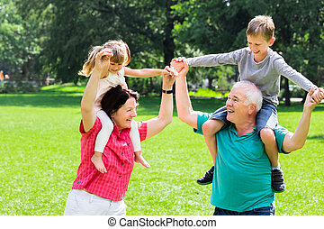Happy Grandparents Giving Grandchildren Piggyback Ride -...