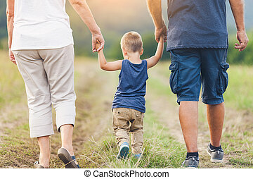 Happy grandparents on a walk with their grandchild